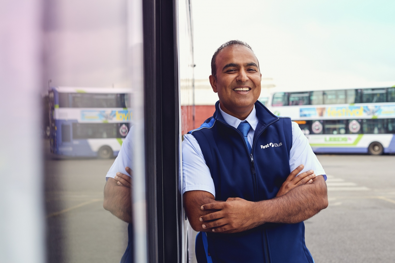 smiling driver leaning against bus