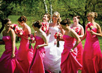 bride in white dress outside with bridesmaids in pink dresses
