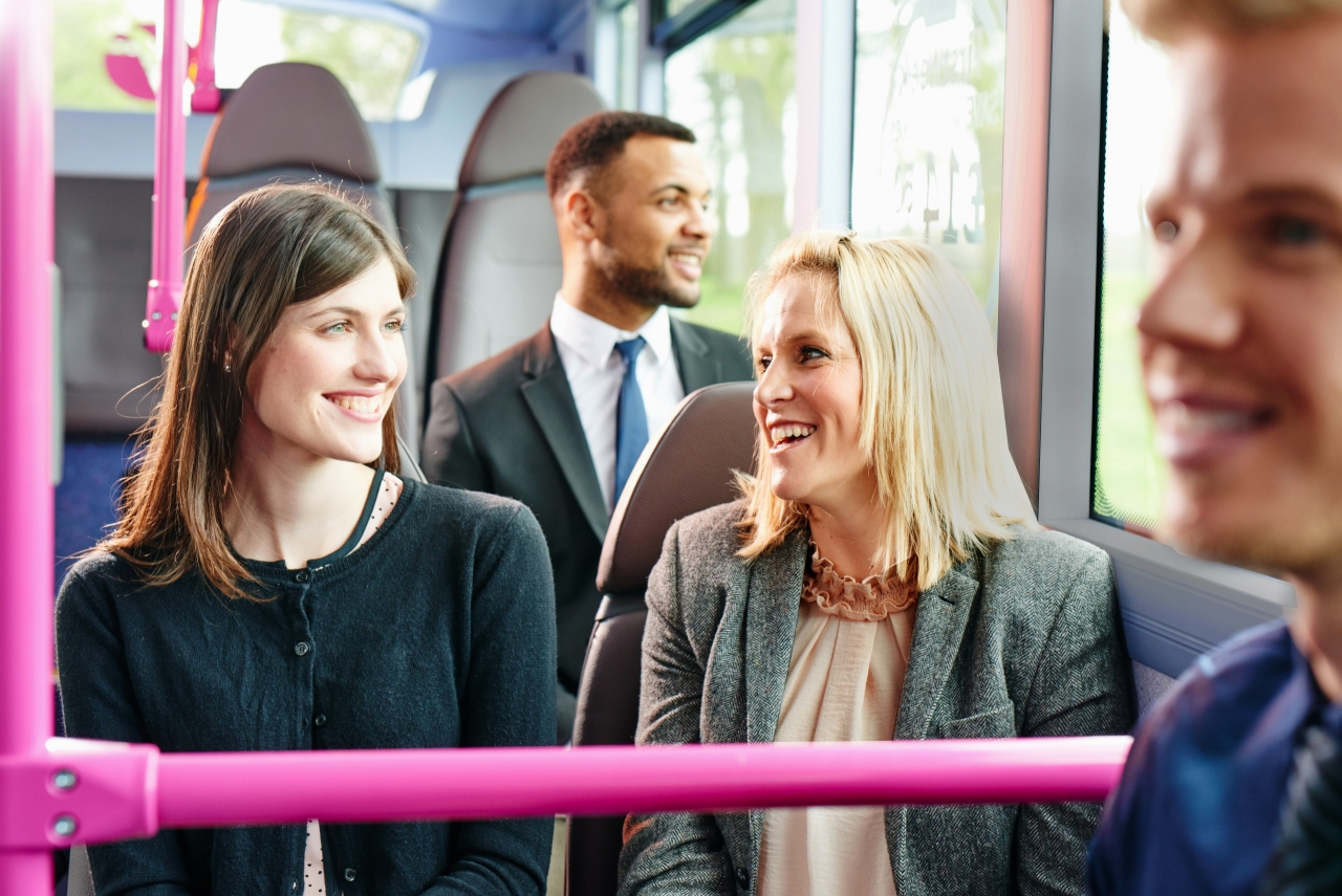 smiling people on a first bus