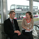 two adults sat at bus station